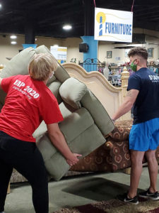 Volunteers helping move furniture at Lighthouse Ministries