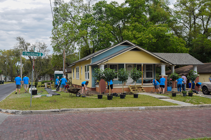 Volunteers working on exterior of house for Neighborhood Revitalization program